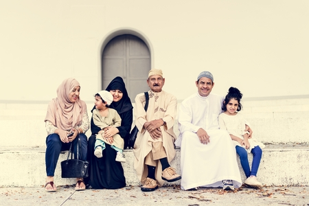 Muslim family sitting together outdoors