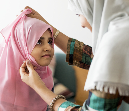Muslim mother putting on a hijab on her little daughter Stok Fotoğraf