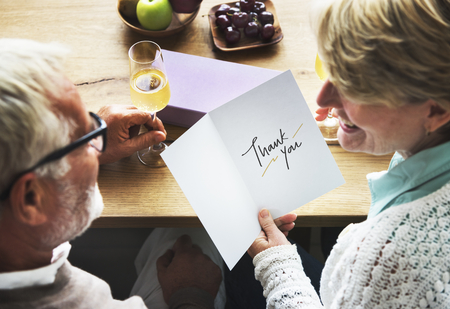 Mature couple holding a thank you card