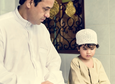 Muslim boy learning how to Salah Stock Photo