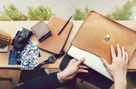 Man pulling out a laptop out of a leather case Stok Fotoğraf - 102861538