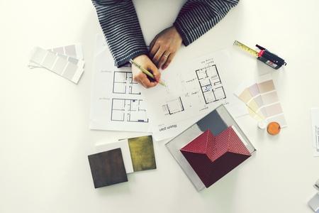 Woman sketching on a blueprint Standard-Bild - 102863915