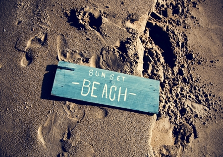 Wooden sign on the sand