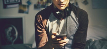 Teenage boy in a bedroom listening to music through his smartphone Stock Photo