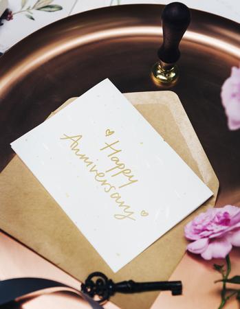 Feminine flat lay of a Happy Anniversary card
