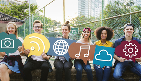Young diverse friends holding social media icons Stock Photo