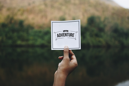 Traveler holding up a note in nature mockup