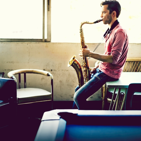 A musician guy playing saxophone alone