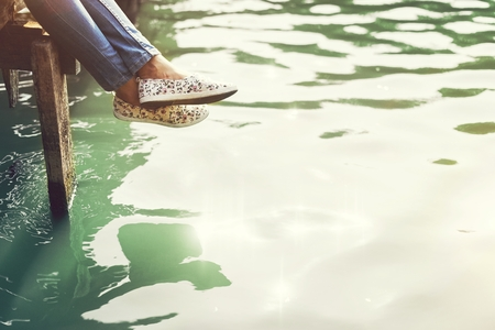Girl sitting by a lake