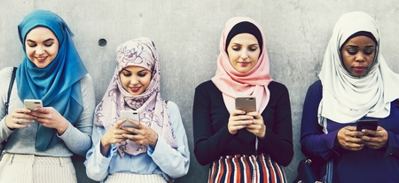 Group of Muslim girls using smartphones Stock Photo