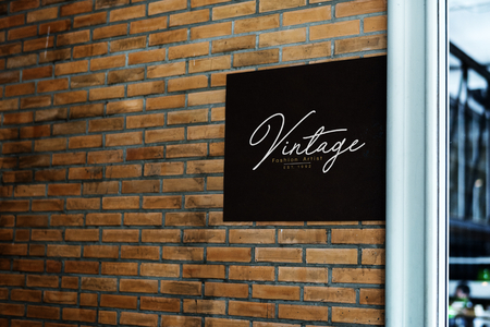 Square black sign on a brick wall mockup Stock Photo