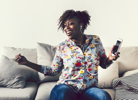 African American woman enjoying music at home
