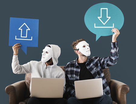 Anonymous hackers holding technology signs Stock Photo