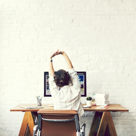 Designer stretching in front of her computer