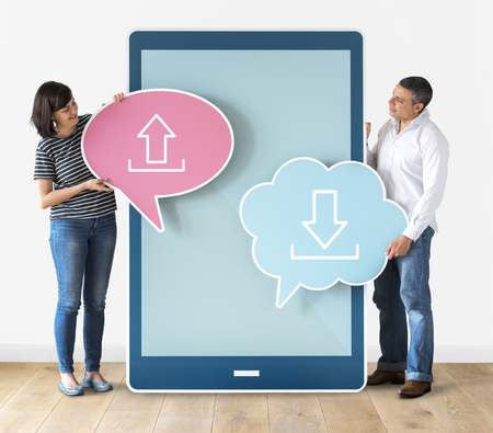 Couple holding speech bubbles and tablet Stock Photo