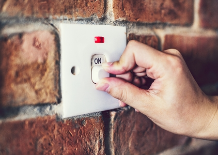 A light switch on a brick wall