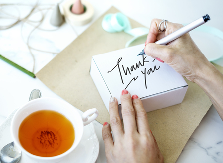 Woman writing Thank You on a white box