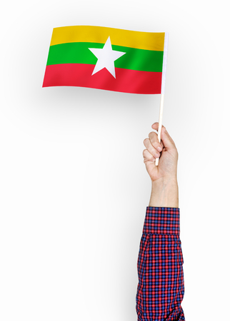 Person waving the flag of Republic of the Union of Myanmar
