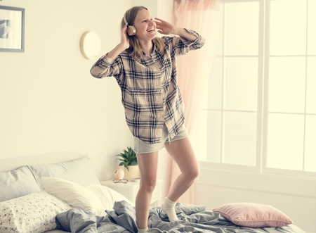 Caucasian girl dancing on bed
