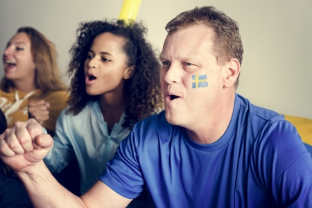 Friends cheering football with painted flag Standard-Bild - 103959714