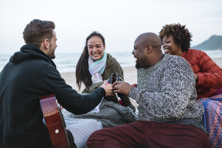Diverse friends drinking beers at the beach Stock Photo