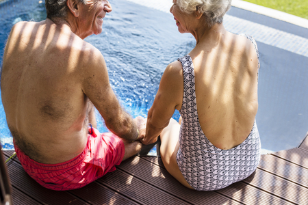 Senior couple holding hands by the swimming pool Stock Photo