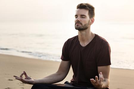 Mann, der Yoga am Strand praktiziert Standard-Bild