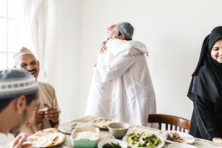 Muslim men hugging at lunchtime