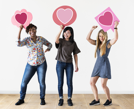 Cheerful women holding heart icons Stock Photo