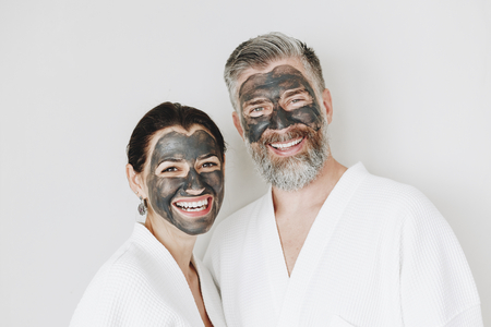Happy couple wearing a charcoal mask Stock Photo