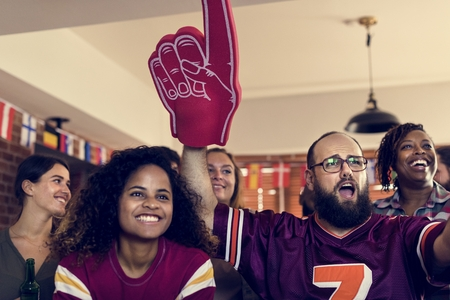 Friends cheering sport at bar together Imagens
