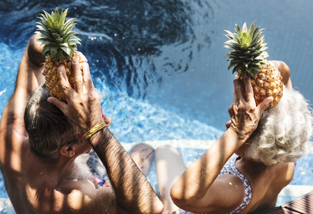 Couple holding pineapples above their heads 写真素材