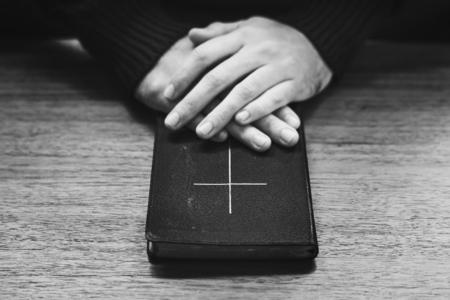 Manos sobre la santa biblia Foto de archivo - 104050068