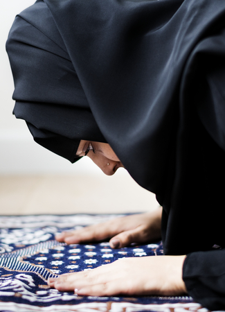 Muslim woman praying in the mosque during the Ramadan