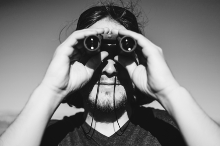 Young backpacker using pair of binoculars