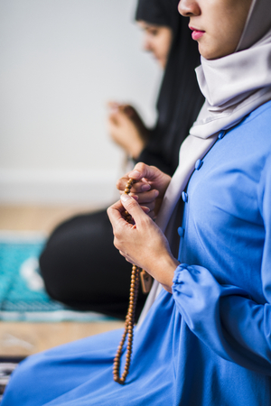 Muslim women using misbaha to keep track of counting in tasbih