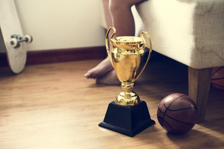 Closeup of trophy on the bedroom floor with basketball