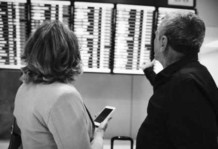 Senior couple checking the flight schedule