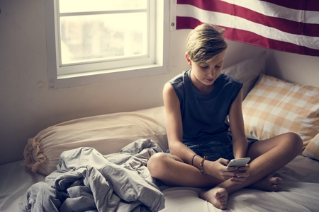 Young caucasian boy sitting using mobile phone on bed