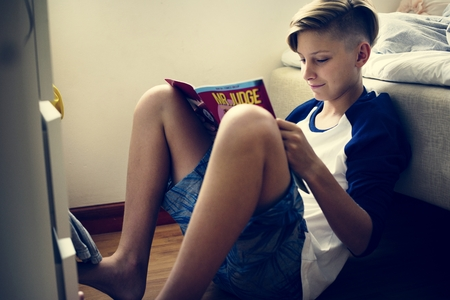 Closeup of young caucasian man sitting on the floor reading cartoon Фото со стока - 104308729