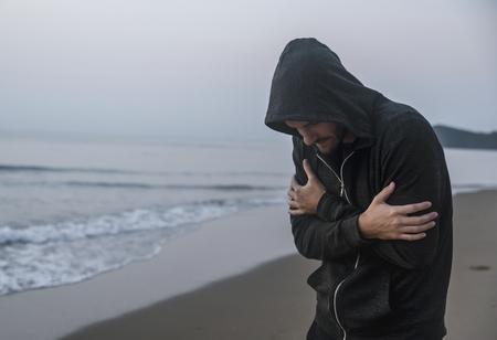 Caucasian man walking alone at the beach 版權商用圖片