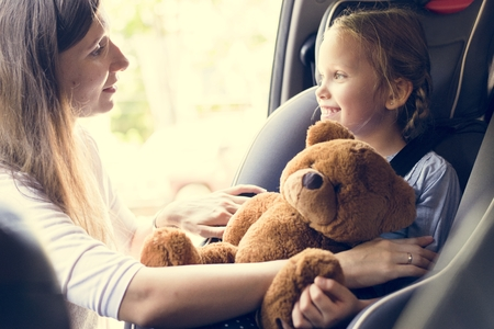 Mother helping to put on the seat belt Stock Photo - 104386786