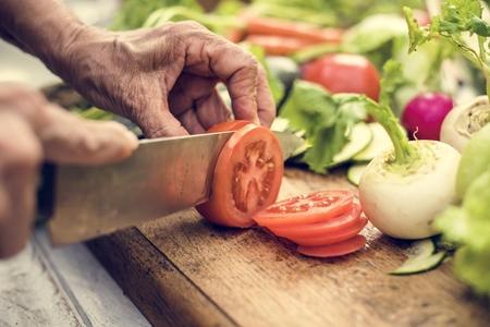 Closeup of hand with knife cutting tomato 版權商用圖片