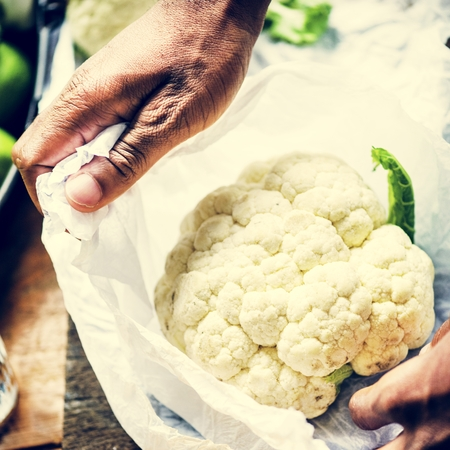 A person handling cauliflower
