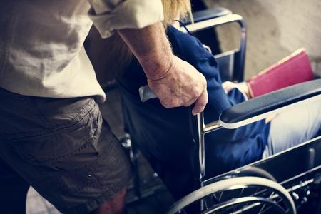 Closeup of senior man pushing the woman wheelchair