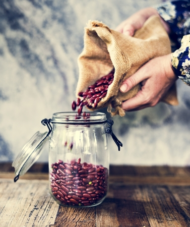 Hands holding sack and pouring beans to the glass jar Stock Photo