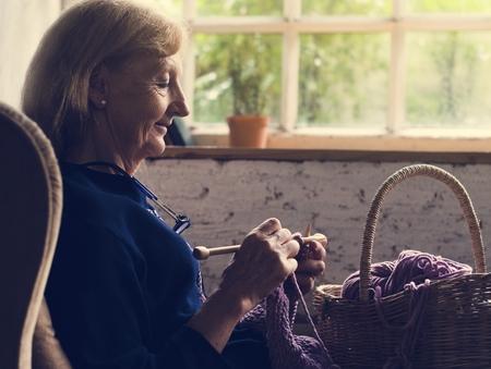 Closeup of senior caucasian woman knitting handicraft hobby Фото со стока
