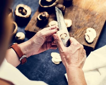 A person slicing portobello mushroom 写真素材