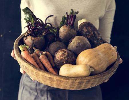 Woman holding various beetroot vegetable in wooden basket