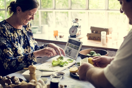 Man and woman in a kitchen preparing a healthy meal Stock Photo
